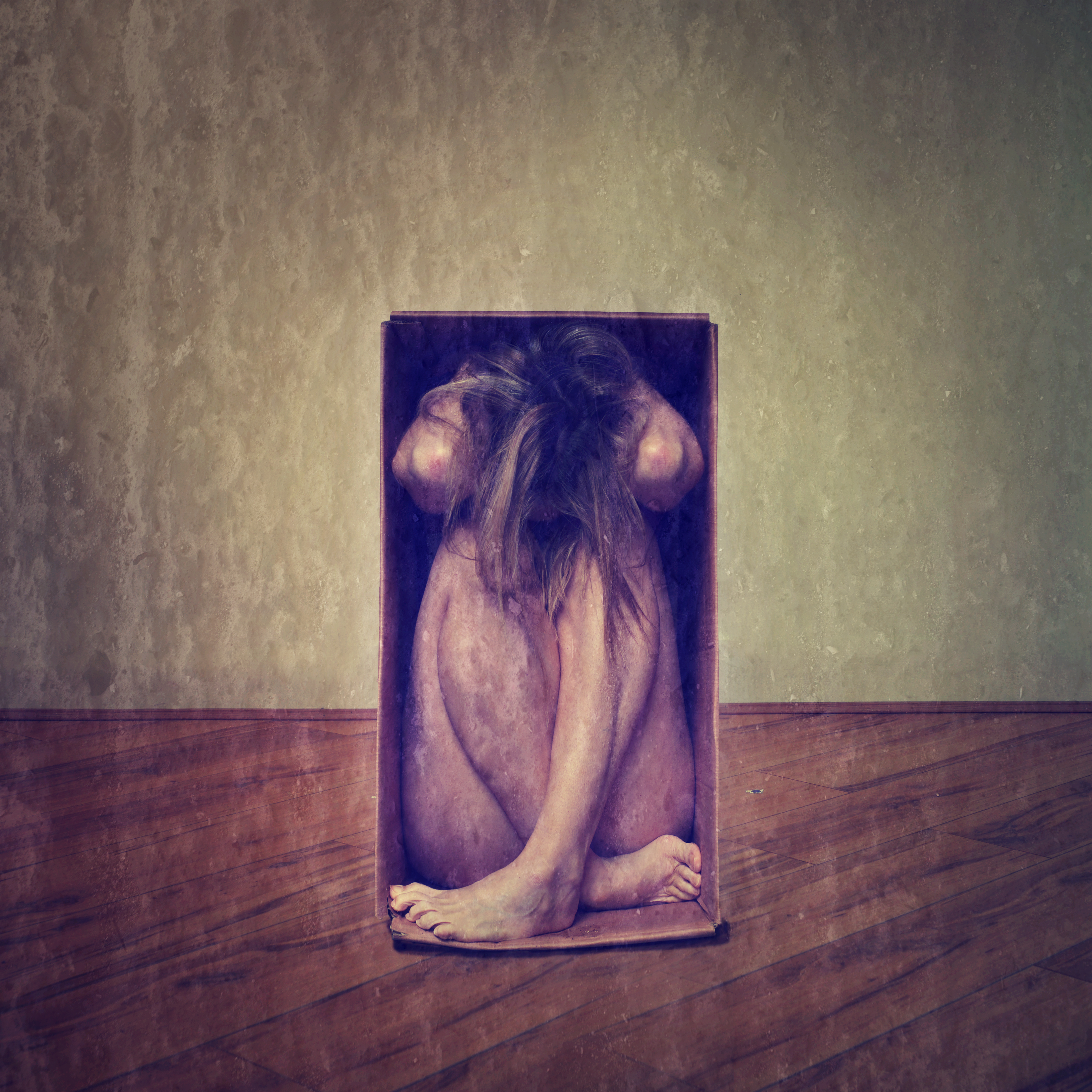 Square frame of woman sat inside a box, crammed in, her hands around her head and her legs crossed.