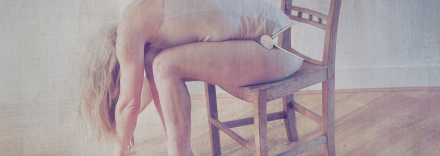 A woman sits bent forward on a wooden chair at a 45 degree angle to the camera. A gold hinge is embedded at her waist, allowing her to hang lifelessly forward.